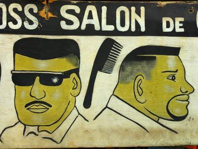 A Hair Salon Sign with Painted Men and Lettering - Photographic Print