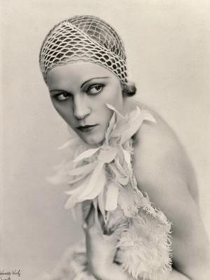 Portrait of a Woman Wearing a Fishnet Hat and a Feather Boa - Photographic Print