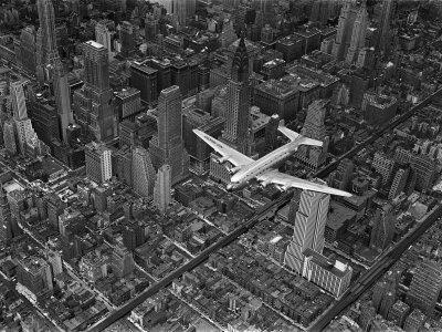 Aerial View of a Dc-4 Passenger Plane in Flight over Manhattan - Photographic Print