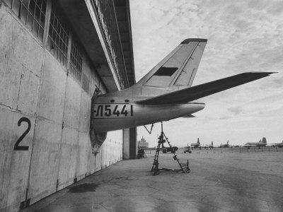 Tail of Soviet Passenger Plane Protruding from Maintenance Hanger - Premium Photographic Print