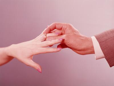 Man Placing Engagement Ring on Woman's Finger - Photographic Print