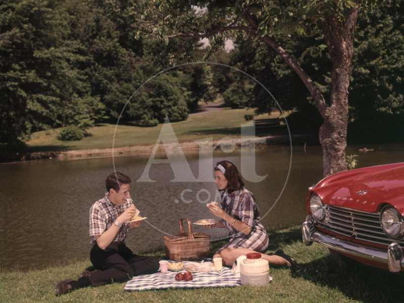 Young Couple Enjoying Picnic Near Lake in Spring