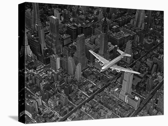 Aerial View of a DC-4 Passenger Plane Flying over Midtown Manhattan-Margaret Bourke-White-Stretched Canvas Print