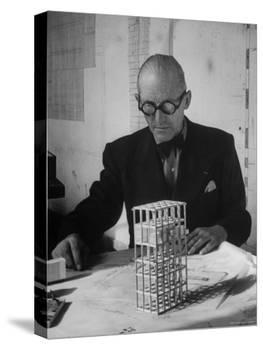 Architect Le Corbusier Studying Architectural Plans and Small Model of Building in His Office-Nina Leen-Premier Image Canvas
