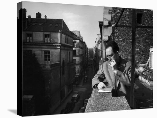 French Writer Albert Camus Smoking Cigarette on Balcony Outside His Publishing Firm Office-Loomis Dean-Stretched Canvas Print