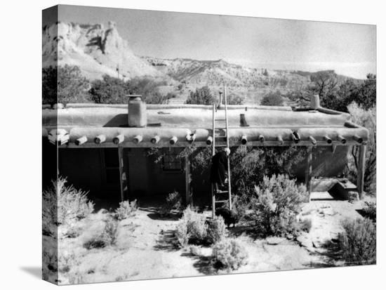 Georgia O'Keeffe Climbing a Ladder Outside Ghost Ranch, Her Desert Home-John Loengard-Stretched Canvas Print