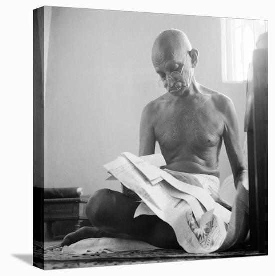 Indian Leader Mohandas Gandhi Reading as He Sits Cross Legged on Floor, at Home-Margaret Bourke-White-Stretched Canvas Print