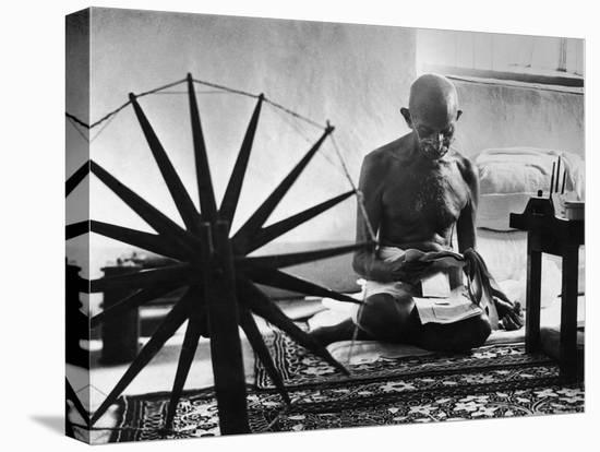 Indian Leader Mohandas Gandhi Reading as He Sits Cross Legged on Floor-Margaret Bourke-White-Stretched Canvas Print