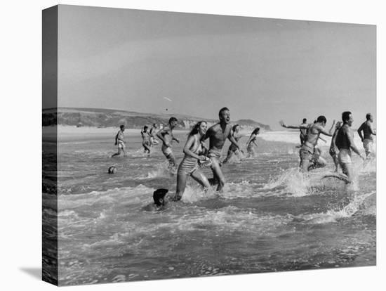 Lifeguards and Members of Womens Swimming Team Start Day by Charging into Surf-Peter Stackpole-Stretched Canvas Print