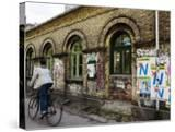 Cyclist in Freetown Christiania  with Anti European Union Posters on Wall