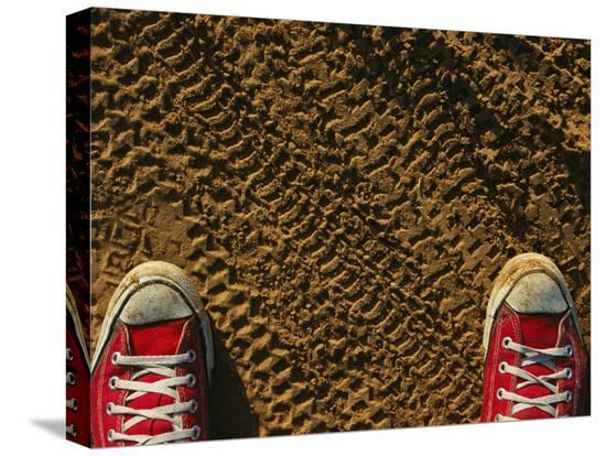 joel-sartore-red-sneakers-on-soil-patterned-with-tire-tracks