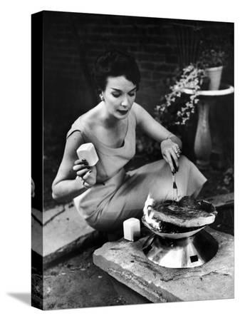 peter-stackpole-well-dressed-woman-cooking-a-large-steak-on-the-aluminum-disposable-barbecue-grill