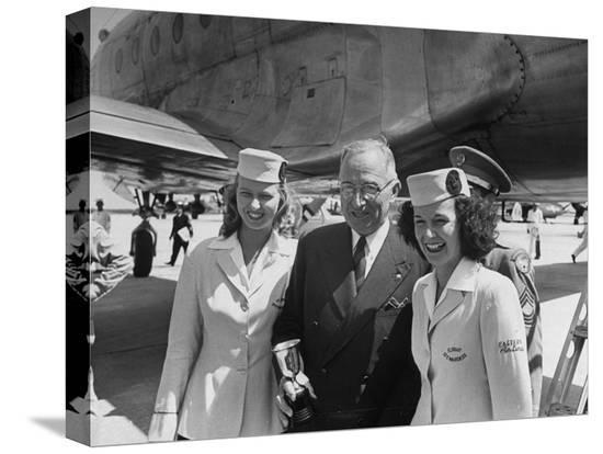 president-harry-s-truman-standing-near-a-plane-flanked-by-stewardesses