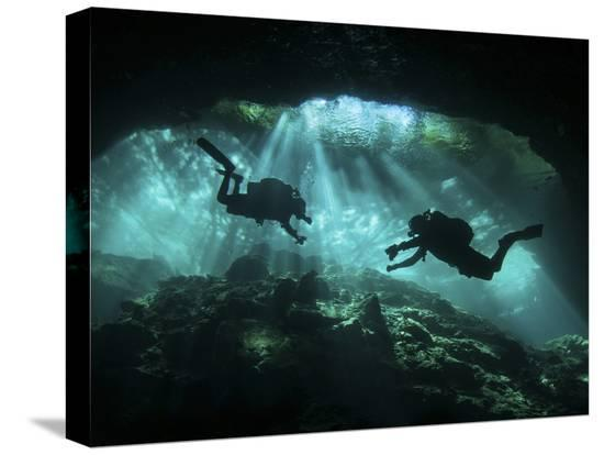 two-divers-silhouetted-in-light-at-entrance-to-chac-mool-cenote-mexico