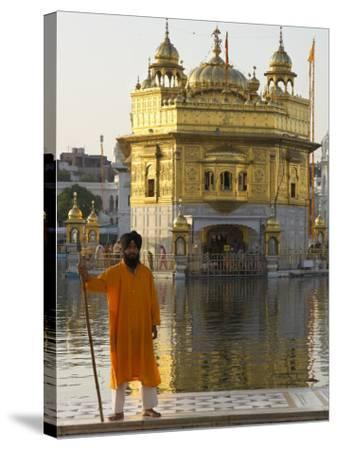 Shrine Guard in Orange Clothes Holding Lance Standing by Pool in Front of the Golden Temple-Eitan Simanor-Stretched Canvas Print