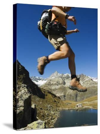 Hiker Running on Trail Above Lake at Schwarzee Paradise, Zermatt Alpine Resort, Valais, Switzerland-Christian Kober-Stretched Canvas Print