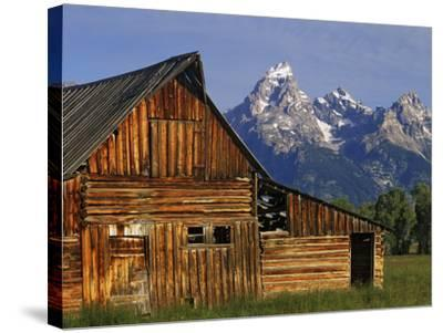 Weathered Wooden Barn Along Mormon Row with the Grand Tetons in Distance, Grand Teton National Park-Dennis Flaherty-Stretched Canvas Print