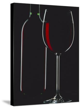 Studio Shot of Back-Lit Glass and Bottle of Red Wine-Lee Frost-Stretched Canvas Print