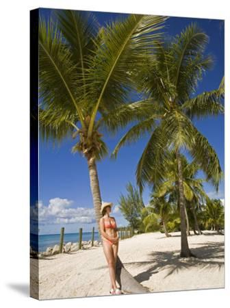Woman Leaning Against Palm Tree, Princess Cays, Eleuthera Island, West Indies, Caribbean-Richard Cummins-Stretched Canvas Print