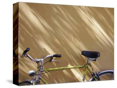 Bicycle Leaning against a Shadowed Yellow Wall, Parma, Italy-Gina Martin-Stretched Canvas Print