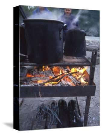 Two Men at Camp Are Drying their Shoes under Camp Cook Fire-Kate Thompson-Stretched Canvas Print