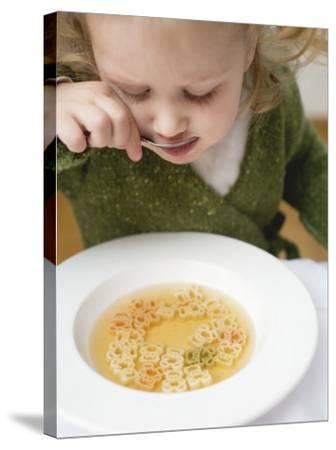 Small Girl Eating Soup with Teddy Bear Pasta--Stretched Canvas Print
