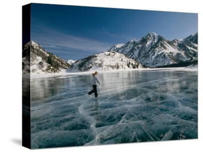 A Girl Ice Skates Across a Frozen Mountain Lake-Michael S^ Quinton-Stretched Canvas Print