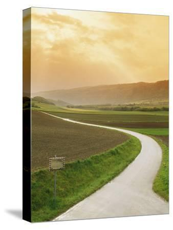 The Golden Sun Glows Through Cloud Cover to Illuminate a Country Road-Richard Nowitz-Stretched Canvas Print