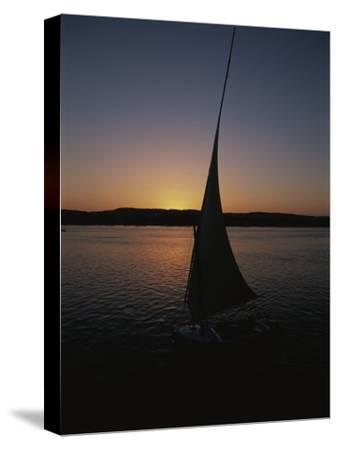 Sunset Outlines the Curve of a Felucca Sail on the Nile River-Stephen St^ John-Stretched Canvas Print