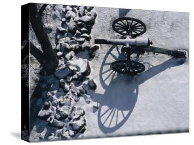 Fresh Snowfall Outlines a Cannon in This Winter View of Gettysburg-Stephen St^ John-Stretched Canvas Print
