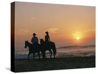 Two People on Horseback Ride Along an Ocean Shoreline at Sunset-Roy Toft-Stretched Canvas Print