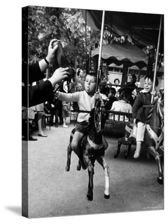 Little Boy on Merry Go Round at the Tuileries Gardens, Sticking Out His Tongue-Alfred Eisenstaedt-Stretched Canvas Print