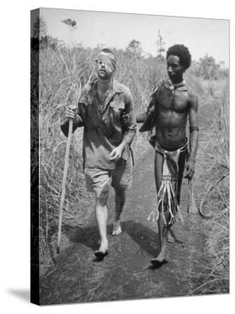 Papuan Native Helping a Wounded Australian Infantryman Along Road Away from the Buna Battlefront-George Silk-Stretched Canvas Print
