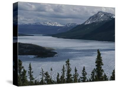 Snow-Capped Moutains Rise Above a Frozen Waterway on Kodiak Island-George F^ Mobley-Stretched Canvas Print