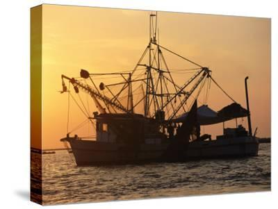 A Shrimp Boat Silhouetted against an Orange Sky--Stretched Canvas Print