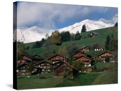 Wooden Chalets on Slope with Snow-Capped Peaks in the Background, Rougemont, Switzerland-Martin Moos-Stretched Canvas Print