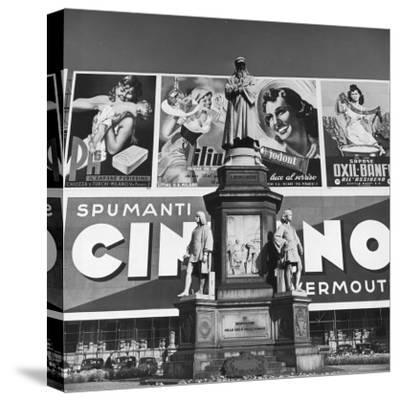 Statue of Leonardo Da Vinci on Top of Monument in Front of Giant Advertising Billboard-Alfred Eisenstaedt-Stretched Canvas Print