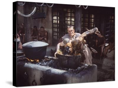 """Kirk Douglas Dunking Enemy's Head in Giant Cook Pot in Scene From Stanley Kubrick's """"Spartacus""""-J^ R^ Eyerman-Stretched Canvas Print"""