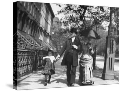 Incredibly Well Dressed Man, Woman and Child Walking by Perfect Brownstone Apartment Buildings-George B. Brainerd-Stretched Canvas Print