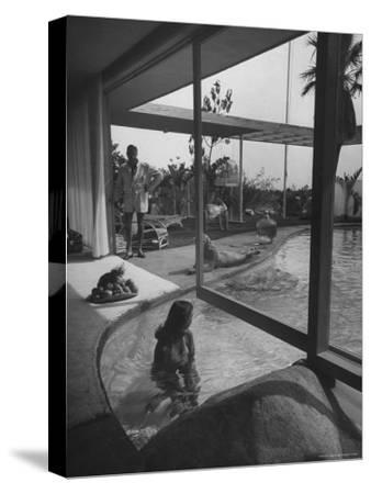 Designer Raymond Loewy Relaxing by Swimming Pool Which Runs from Outdoors Into Living Room-Peter Stackpole-Stretched Canvas Print