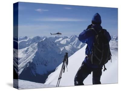 A Back-Country Skier Watches a Heli-Ski Chopper Approach a Peak-Skip Brown-Stretched Canvas Print