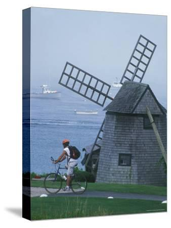 A Man on a Bicycle Passing a Windmill on the Shore in Cape Cod-Darlyne A^ Murawski-Stretched Canvas Print