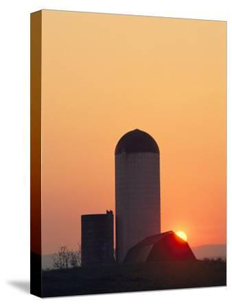 Twilight View of a Barn and Silo Silhouetted against the Sun-Kenneth Garrett-Stretched Canvas Print