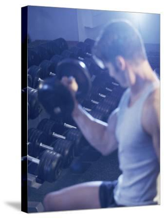 Young Man Exercising with Dumbbells--Stretched Canvas Print