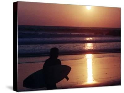 A Surfer is Silhouetted by the Setting Sun as He Leaves the Pacific Ocean on Venice Beach--Stretched Canvas Print