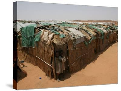 Two Sudanese Boys Stand by Makeshift Huts--Stretched Canvas Print
