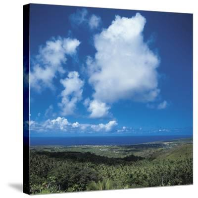 Fluffy White Clouds Over a Blue Ocean and Beach--Stretched Canvas Print