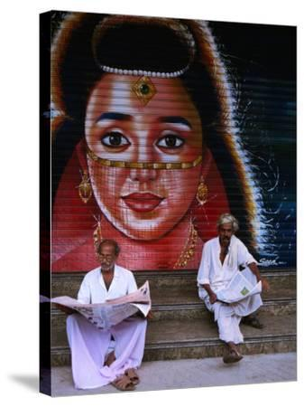 Local Men Read Newspapers in Front of Painted Shutter, Kozhikode, Kerala, India-Greg Elms-Stretched Canvas Print