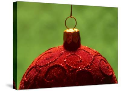 Close-Up of Red Christmas Decoration with Glitter Pattern Against Green Background--Stretched Canvas Print