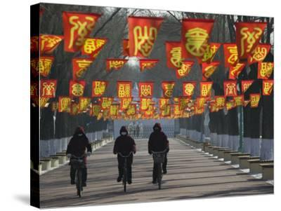 Bicycle Riders at Entranceway to Festival, Ice and Snow Festival, Harbin, Heilongjiang, China-Walter Bibikow-Stretched Canvas Print